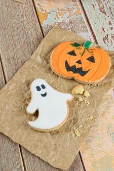 Maślane ciasteczka o tematyce halloween obok okruchów na brązowym papierze.