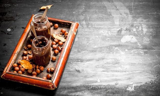 Masło czekoladowe z orzechami laskowymi. na czarnej tablicy.