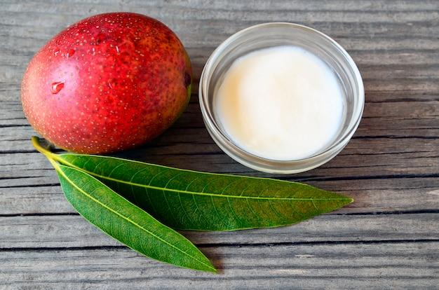 Masło do ciała mango w szklanej misce i świeżych dojrzałych organicznych owocach mango na starym drewnie