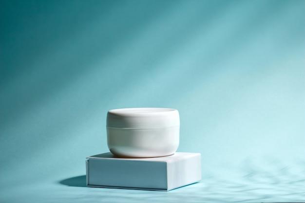Masło do pielęgnacji skóry twarzy i ciała na podium z minerałami morskimi.