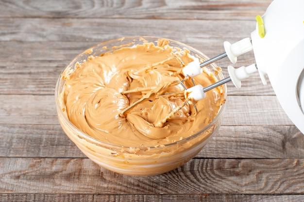 Masło i gotowane mleko skondensowane w szklanej misce z mikserem. robienie kremu do ciasta