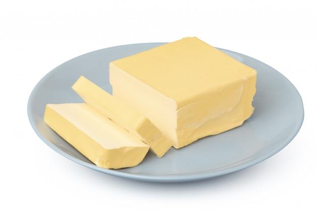 Masło na bielu talerzu odizolowywającym na białym tle