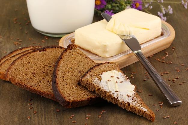 Masło na drewniany uchwyt otoczony chlebem i mlekiem na drewnianym stole z bliska