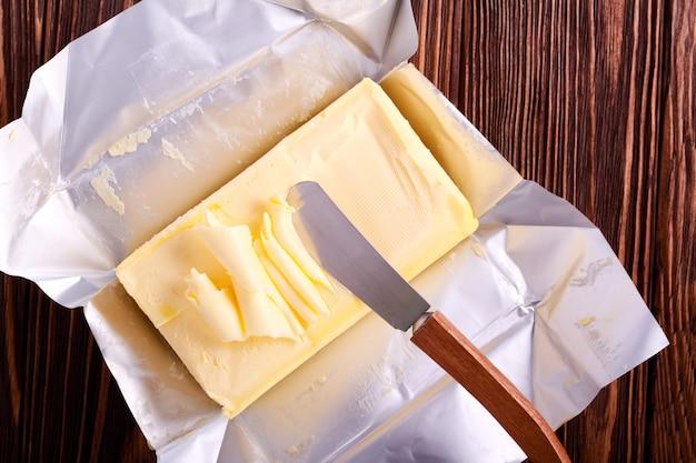 Masło na papierowym opakowaniu na drewnianym stole