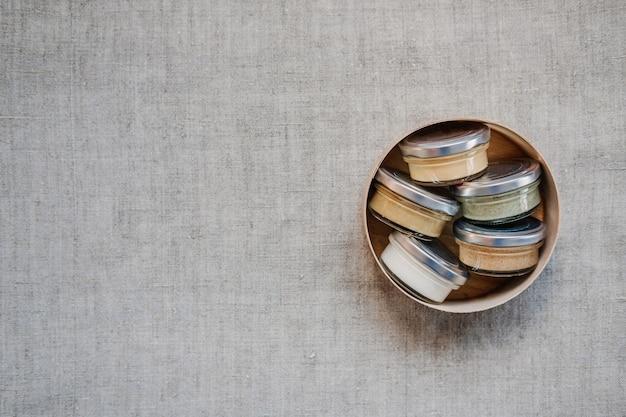 Masło orzechowe i nasiona w szklanych słoikach na tle naturalnej tkaniny z domowym surowym ekologicznym copyspace