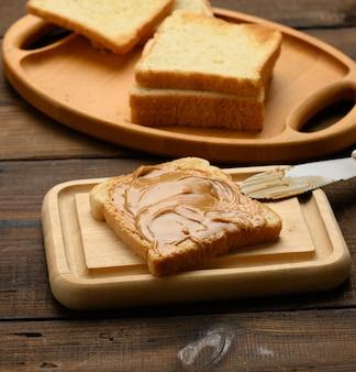 Masło orzechowe na kwadratowym kawałku białej mąki pszennej, śniadanie, widok z góry