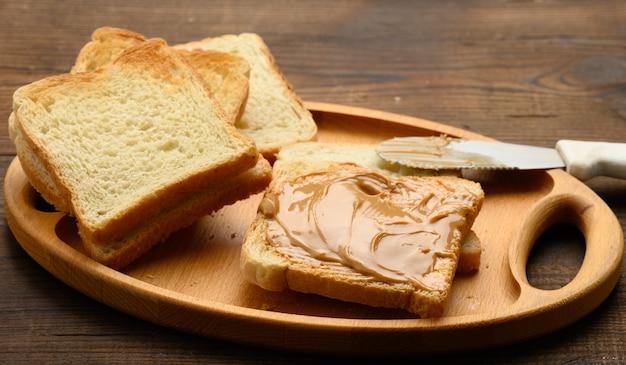 Masło orzechowe na kwadratowym kawałku białej mąki pszennej, śniadanie