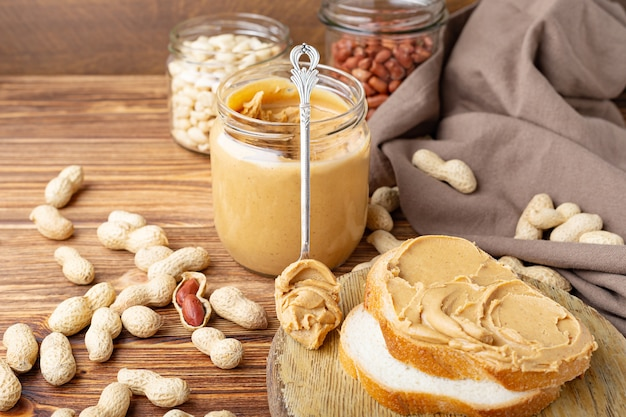 Masło orzechowe w łyżce w pobliżu kremowej pasty orzechowej w otwartym szklanym słoju i tosty z masłem orzechowym.