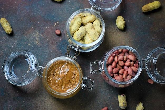 Masło orzechowe w słoiku i orzeszki ziemne w słoikach