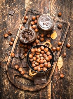 Masło orzechowe z czekoladą i orzechami laskowymi. na drewnianym tle.