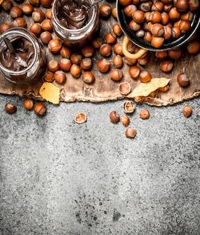 Masło orzechowe z orzechów laskowych i czekolady. na tle rustykalnym.