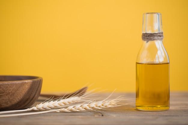 Masło pszenne w butelce, pszenne uszy, łyżka i talerz na drewnianym stole na żółtym tle. skopiuj miejsce