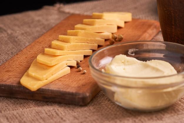 Masło, sery i mleko na śniadanie, nad nieociosanym drewnianym tłem z kopii przestrzenią.