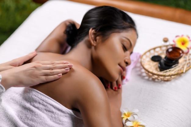 Masowanie pleców przez masażystkę pięknej międzyrasowej dziewczyny leżącej na stole do masażu