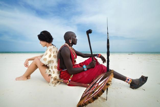 Massai i biała kobieta na plaży
