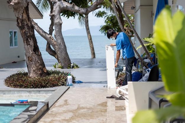 Master men czyści klimatyzator w tropikalnym hotelu.