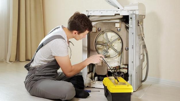 Master otwiera tylny panel zepsutej pralki przy ścianie