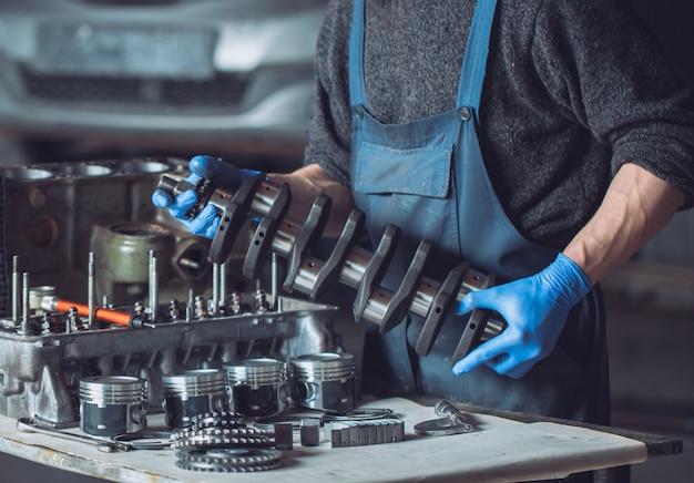 Master zbiera przebudowany silnik do samochodu.