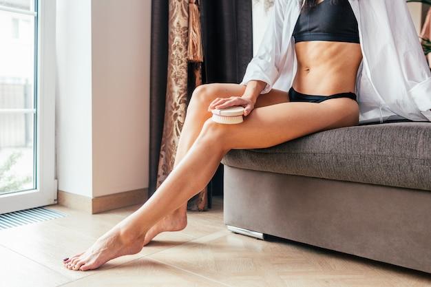 Masuj suchą szczotką. dziewczyna w białej koszuli masuje nogi, antycellulit, peeling, zabiegi kosmetyczne. domowa pielęgnacja skóry.