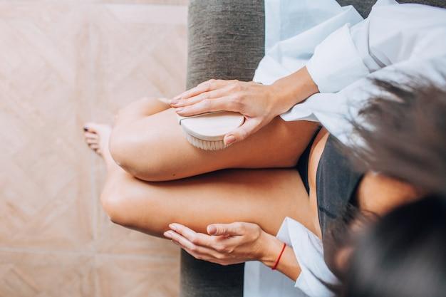 Masuj suchą szczotką. dziewczyna w białej koszuli masuje nogi z bliska na kanapie, spa, relaks, antycellulit, peeling, zabiegi kosmetyczne