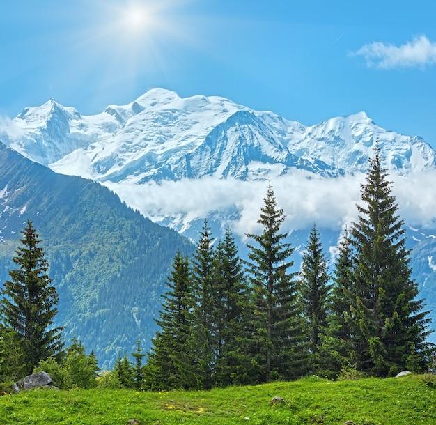 Masyw górski mont blanc ze słońcem w błękitne niebo (dolina chamonix, francja, widok z obrzeży plaine joux).
