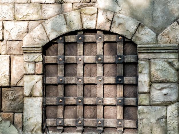 Masywna stara drewniana brama z łukiem w ścianie wykonana z dużych kamieni