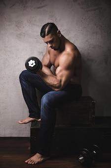 Masywny, brutalny kulturysta wykonujący ćwiczenia na biceps z hantlami
