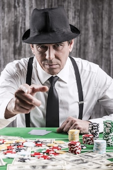 Masz dla mnie pieniądze! poważny starszy mężczyzna w koszuli i szelkach siedzi przy stole pokerowym i wskazuje na ciebie, podczas gdy wokół niego leżą pieniądze i żetony do gry