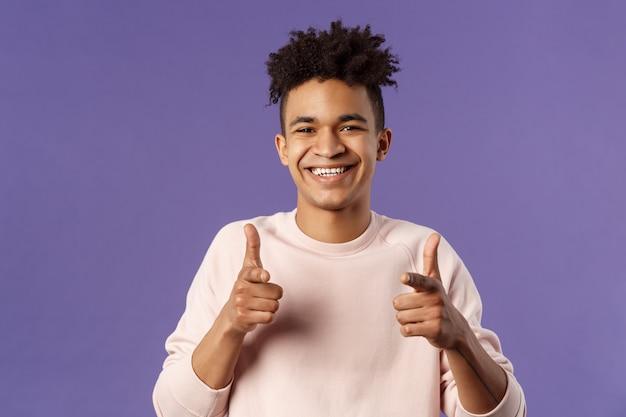 Masz to. szczegół portret uśmiechniętego ślicznego młodego latynoskiego mężczyzny mówiącego powodzenia, wskazując palcami aparat z zadowolonym uroczym uśmiechem, zachęca osobę ubiegającą się o pracę, łowca głów wybiera nowych kandydatów