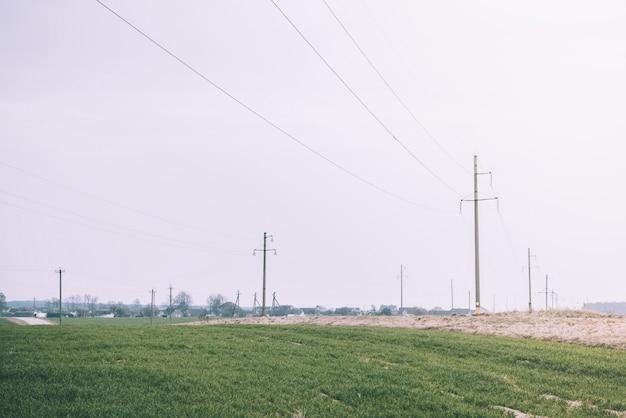 Maszt linii elektroenergetycznej w polu w słoneczny dzień. słup wysokiego napięcia.