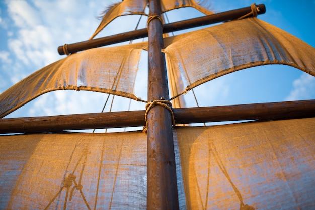 Maszt statku z beżowymi żaglami kołysze się na tle błękitnego nieba