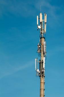 Maszt telekomunikacyjny ustawiony na tle błękitnego nieba i dużej białej chmury