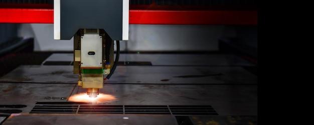 Maszyna do cięcia laserowego głowicy podczas cięcia blachy za pomocą iskrzącego światła w przestrzeni fabrycznej