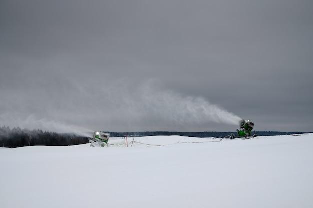 Maszyna do naśnieżania na stoku narciarskim w zimie rozpylanie puchu śnieżnego