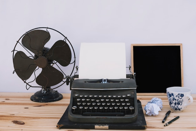 Maszyna do pisania blisko blackboard i fan