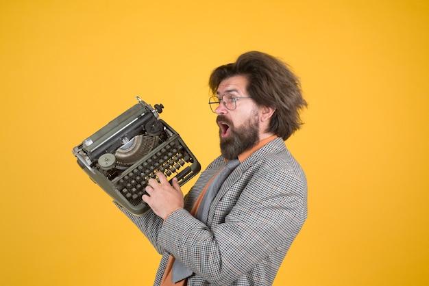 Maszyna do pisania. brodaty nauczyciel trzyma maszynę do pisania. dziennikarz trzyma maszynę do pisania. antyki, stary, dziennikarz, sekretarka, seo, menedżer, biznes, szef. pisze na maszynie do pisania.
