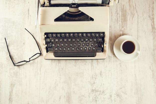 Maszyna do pisania i okulary z kawą na drewnianym stole