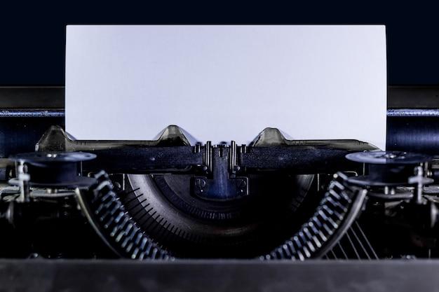 Maszyna do pisania na czarnym tle z wyraźną białą stroną. orientacja pozioma