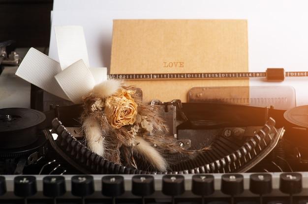 Maszyna do pisania z bliska i suszy kwiaty z kopertą. vintage papier stonowany i kraft