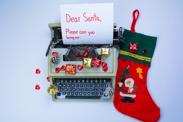 """Maszyna do pisania z napisem """"drogi mikołaju"""", pudełka upominkowe i gałęzie jodły na białym tle"""