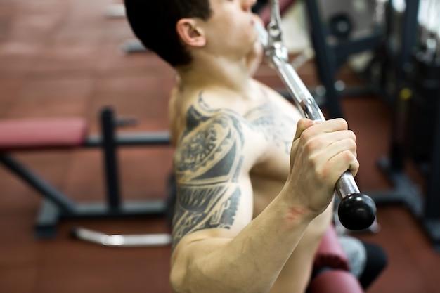 Maszyna do ściągania ramion. fitness człowiek poćwiczyć lat pulldown szkolenia na siłowni. ćwiczenia siłowe górnej części ciała dla górnej części pleców.