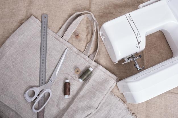 Maszyna do szycia, domowy eko shopper, nożyczki i nić na lnianym materiale, widok z góry zero waste lifestyle