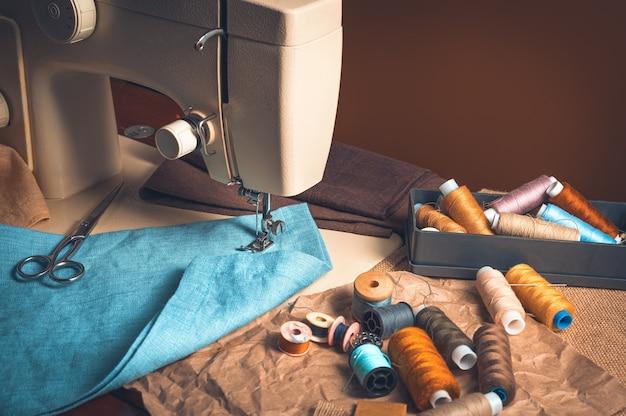 Maszyna do szycia, nici z tkaniny na brązowo barwionym tle.