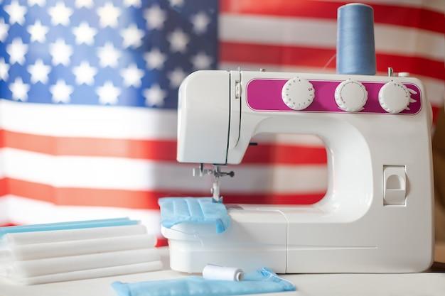 Maszyna do szycia przed amerykańską flagą. koronawirus w stanach zjednoczonych. ręcznie szyte maski medyczne dla szpitali i lekarzy.