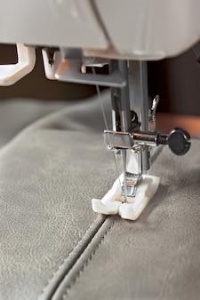 Maszyna do szycia ze specjalną stopką wykonuje szew na szarej skórze. proces szycia z bliska