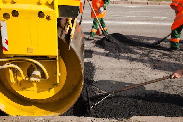 Maszyna do układania świeżego asfaltu lub bitumu na podłożu żwirowym podczas budowy autostrady