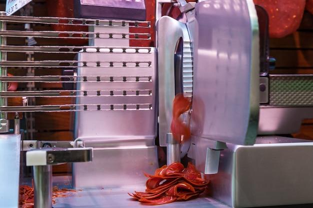 Maszyna tnie cienkie kawałki basturmy. maszyna do krojenia mięsa.