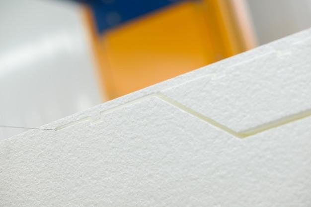 Maszyna tnie plastik piankowy. zakład do produkcji płyt warstwowych ze styropianu. zbliżenie
