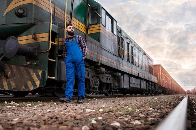 Maszynista stojący przy lokomotywie na stacji kolejowej