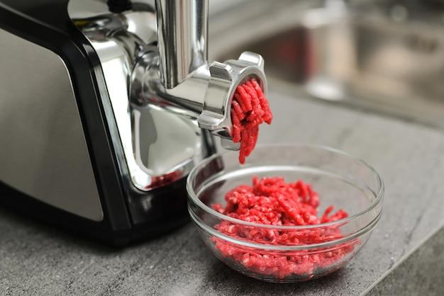 Maszynka do mięsa ze świeżym farszem na stole kuchennym farsz do mięsa i maszynka do mięsa